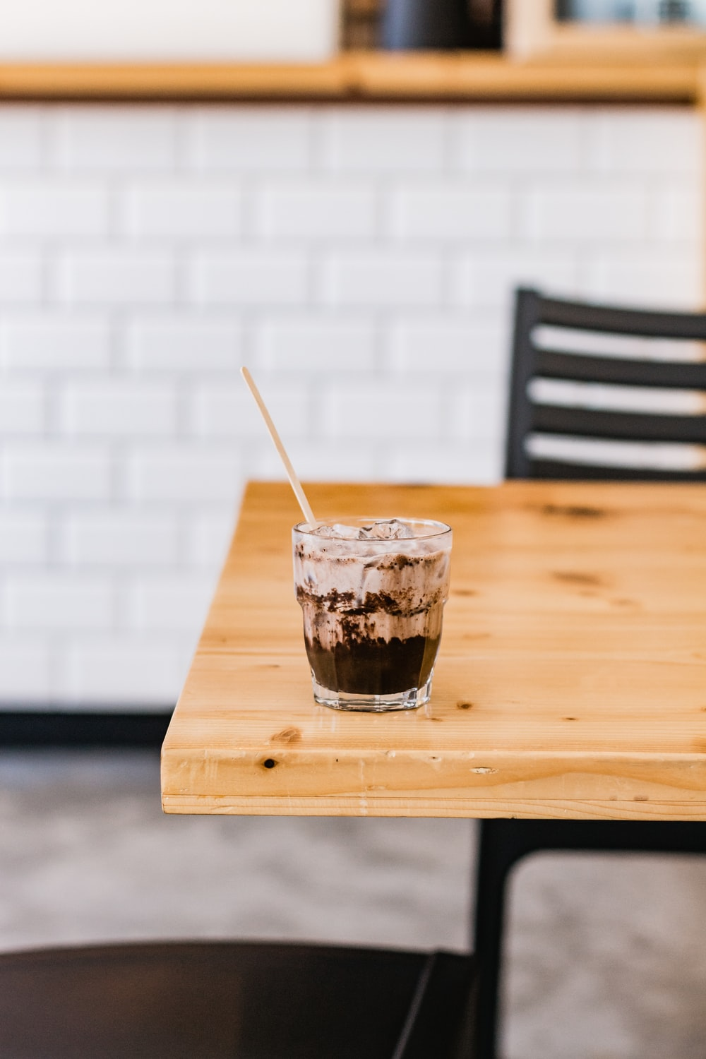 clear drinking glass with black liquid on brown wooden table