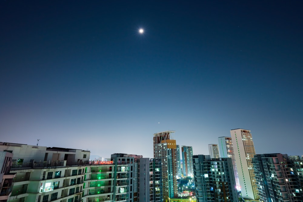 city buildings under blue sky during night time