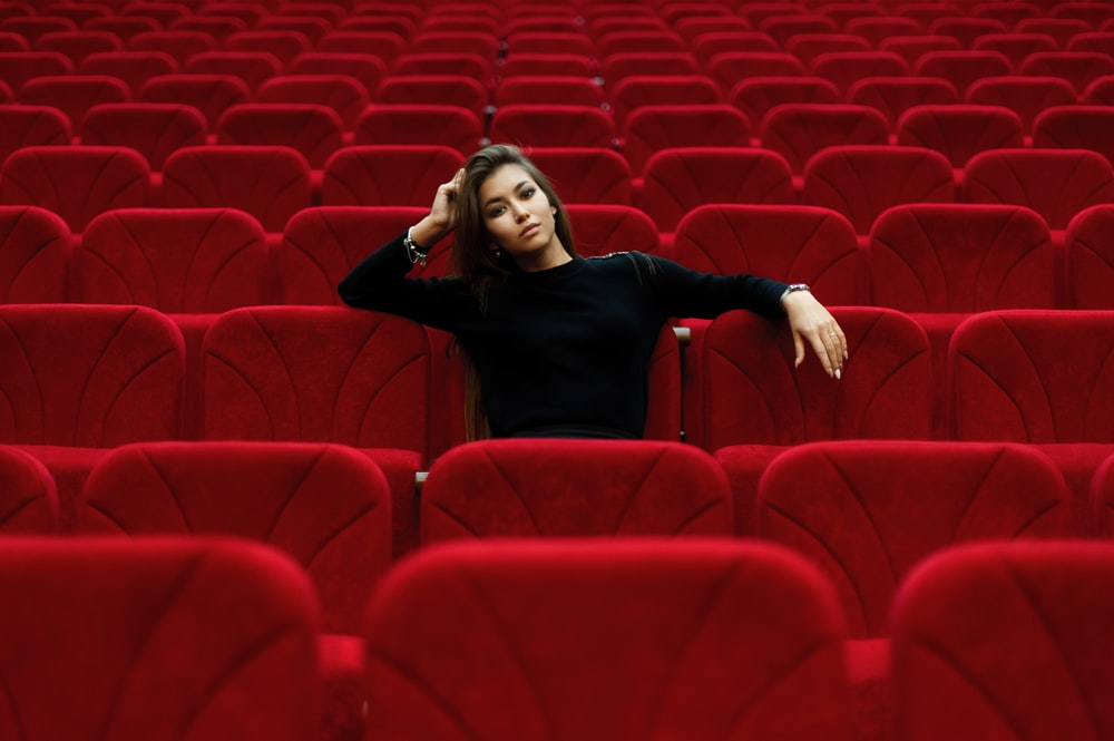 woman in black long sleeve shirt sitting on red chair