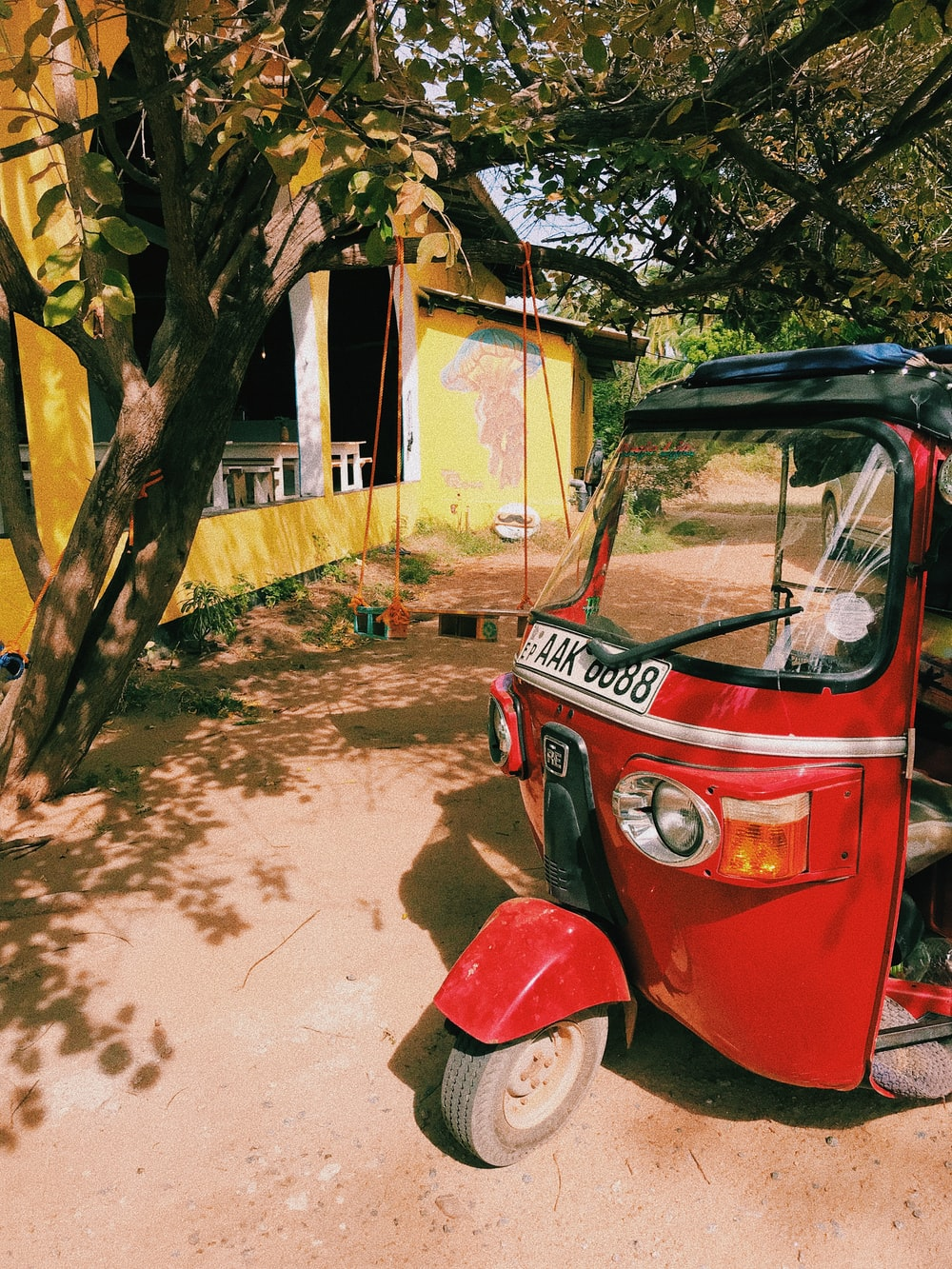 red and black auto rickshaw parked beside green tree during daytime