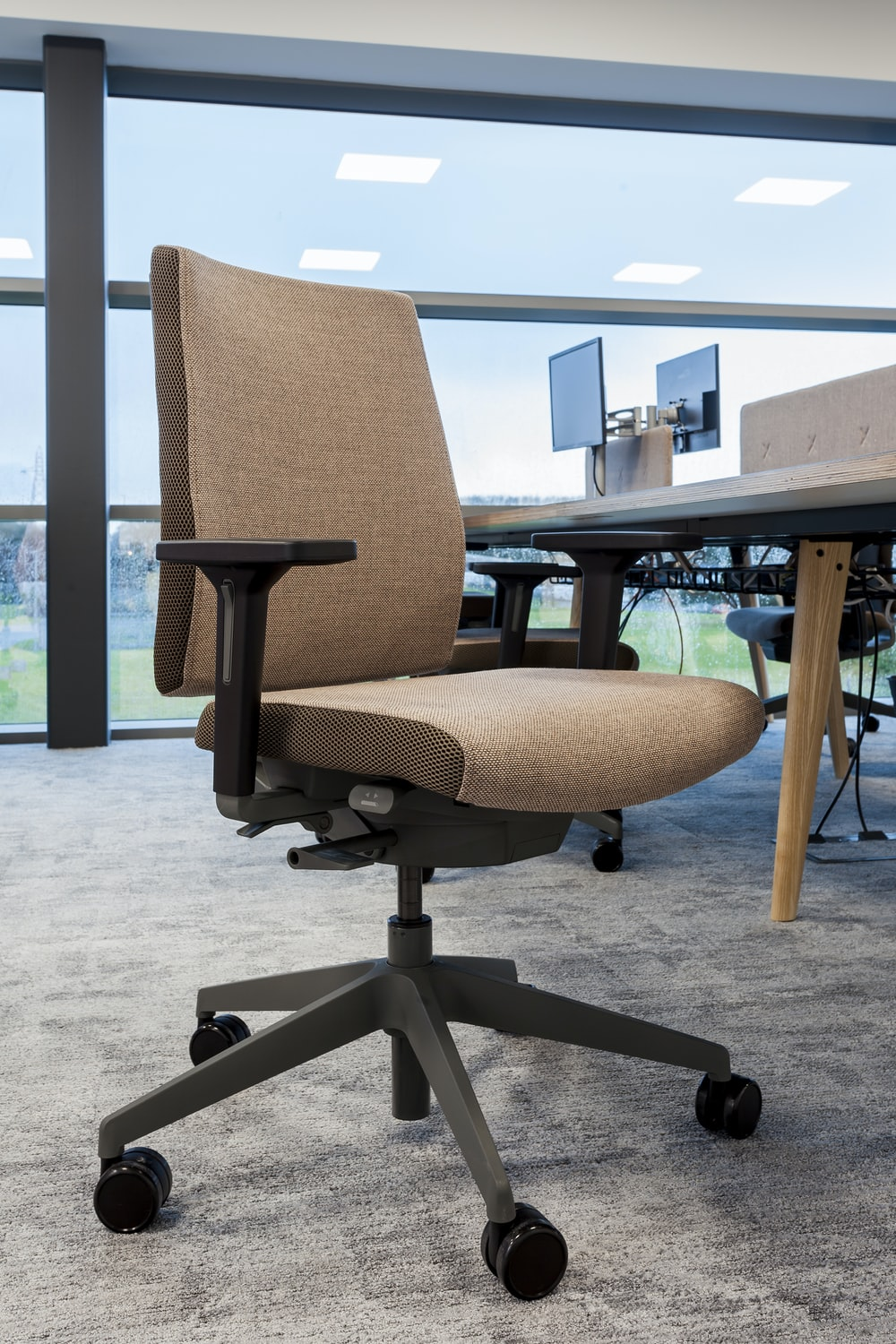 brown office rolling chair near table