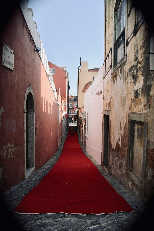 red hallway between brown concrete buildings during daytime