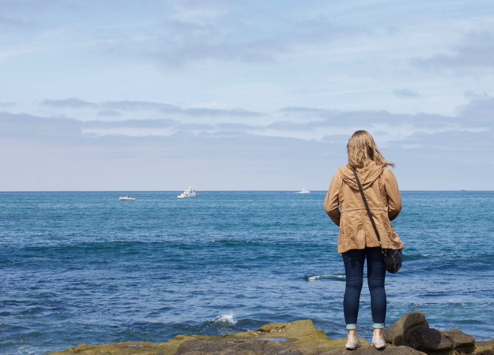 woman in brown jacket standing on rock near sea during daytime