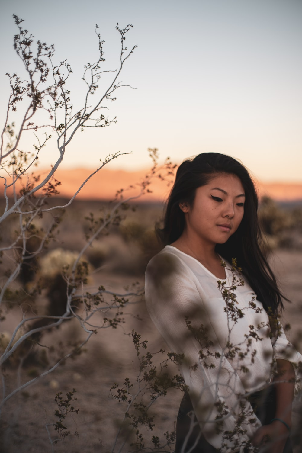 woman in white floral shirt standing near bare tree during sunset