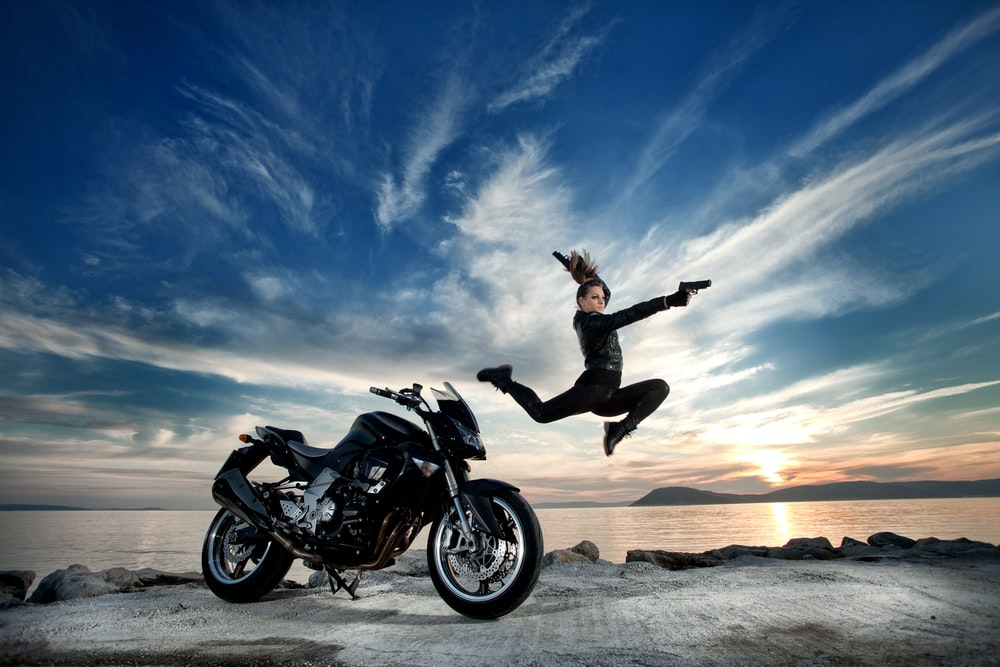 man in black jacket and black pants riding black motorcycle on brown sand during daytime