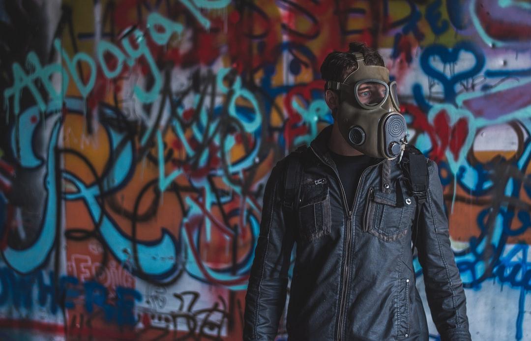 Man In Black Leather Jacket Wearing Gas Mask - unsplash