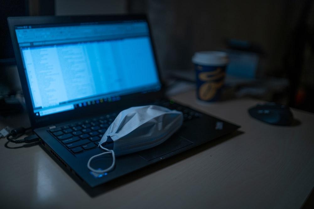 black laptop computer beside black framed eyeglasses on brown wooden table