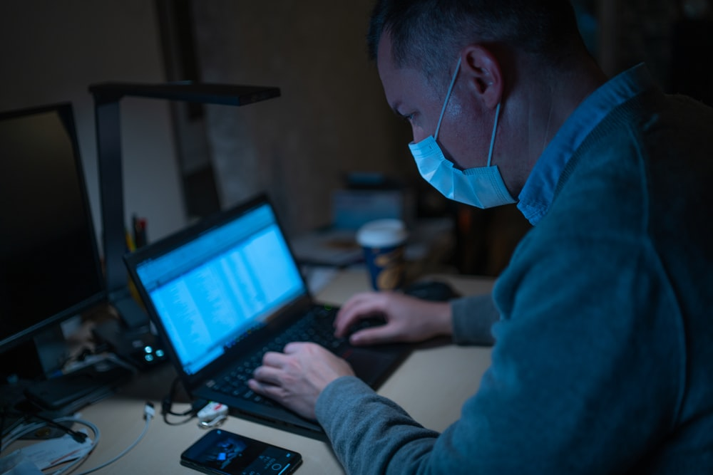 man in blue hoodie using laptop computer