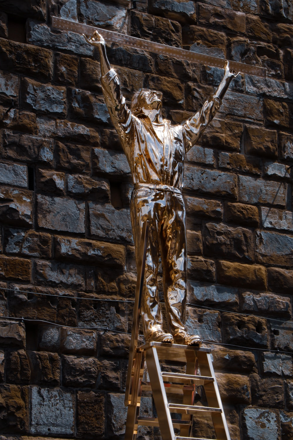 gold statue of man on black brick wall
