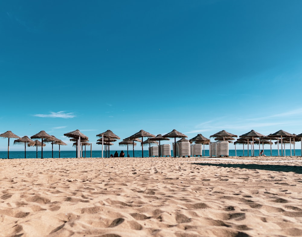 brown and white beach umbrellas on beach during daytime