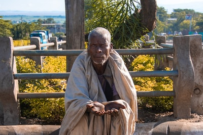man in brown robe sitting on brown wooden bench during daytime ethiopia zoom background