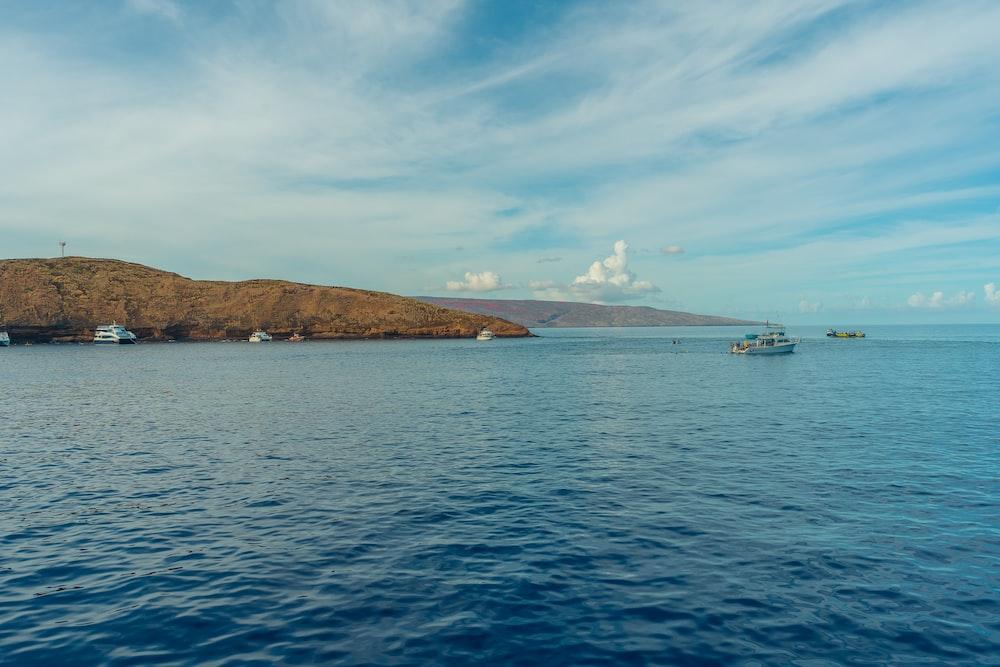 white ship on sea near island under blue sky during daytime