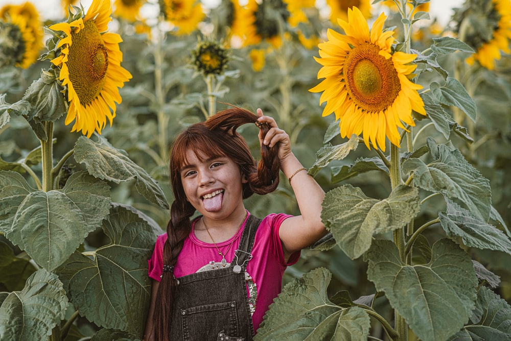 girl in pink and gray tank top standing on sunflower field during daytime