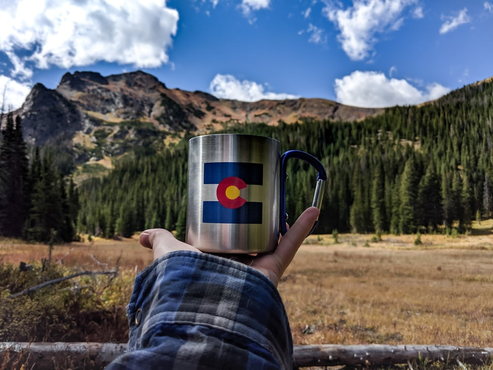 white blue and red ceramic mug on brown grass field
