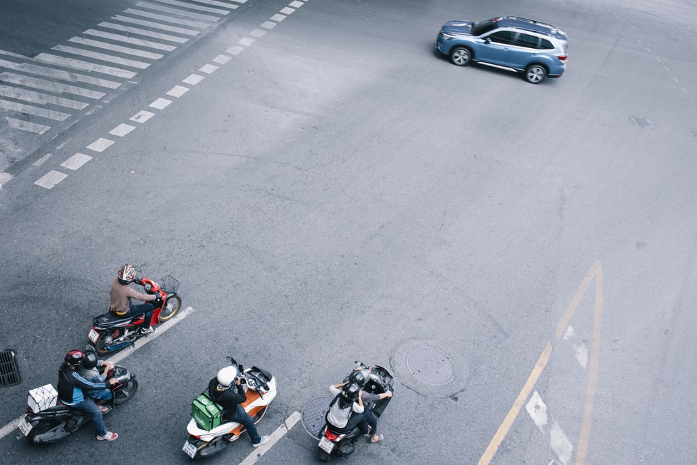 people riding on motorcycle on road during daytime