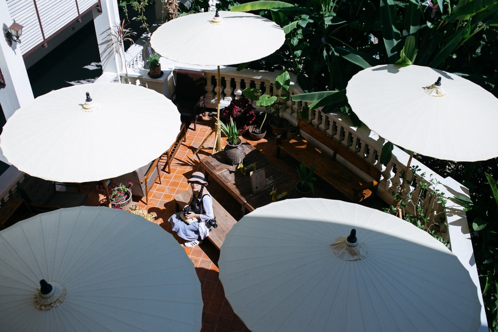people sitting on brown wooden chairs under white umbrella during daytime