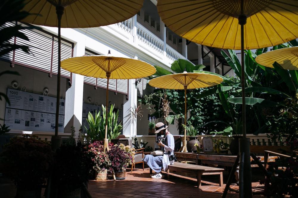 man in blue shirt sitting on brown wooden chair under yellow umbrella during daytime