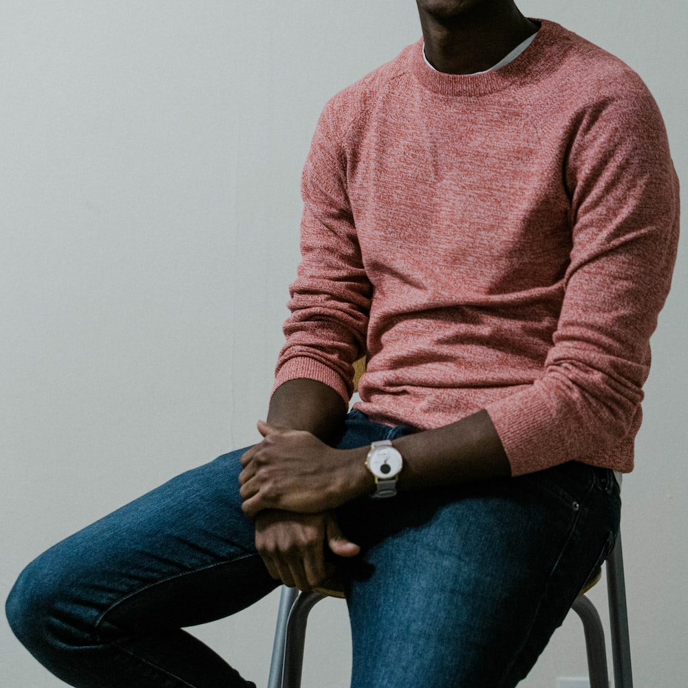 man in brown sweater and blue denim jeans sitting on chair