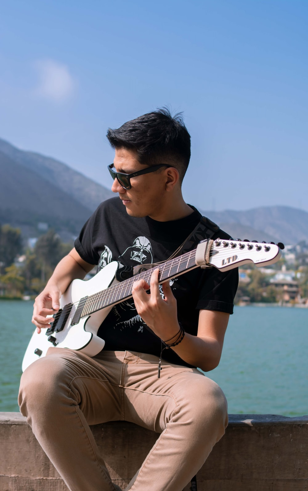 man in black crew neck t-shirt playing white electric guitar