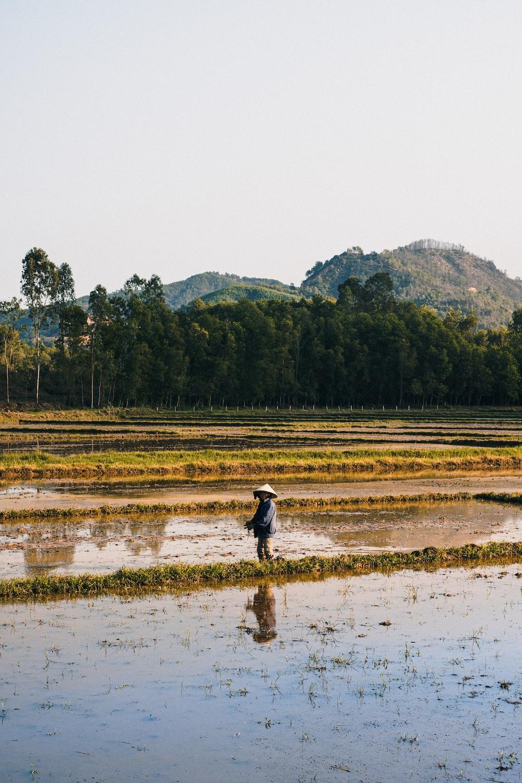 man in black jacket walking on brown field during daytime