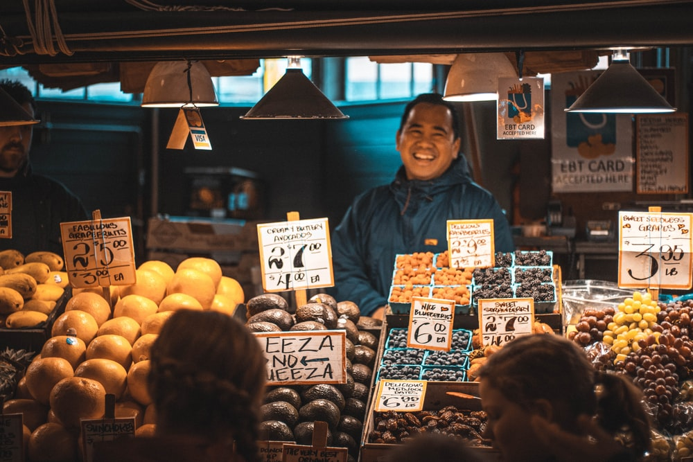 woman in blue jacket standing in front of fruit stand
