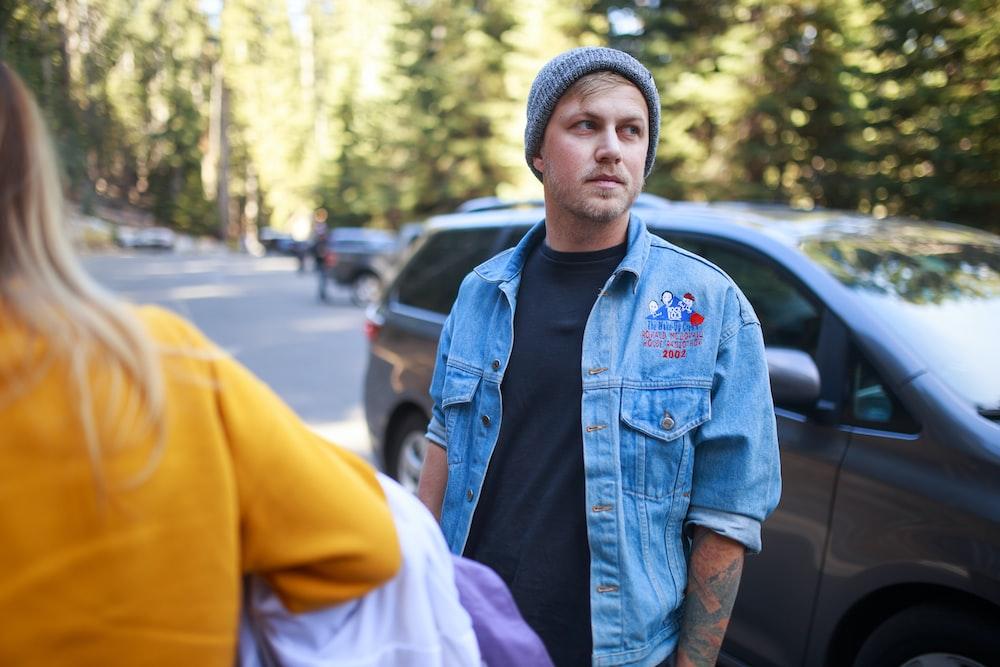 man in blue denim jacket wearing gray knit cap standing near cars during daytime