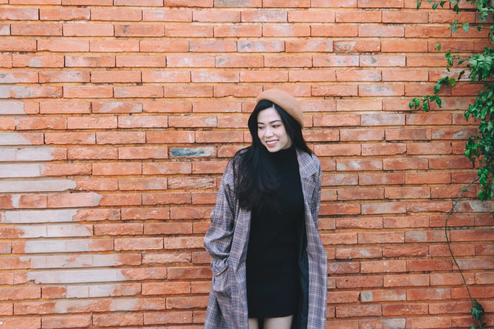 woman in gray scarf and black jacket standing beside brown brick wall during daytime