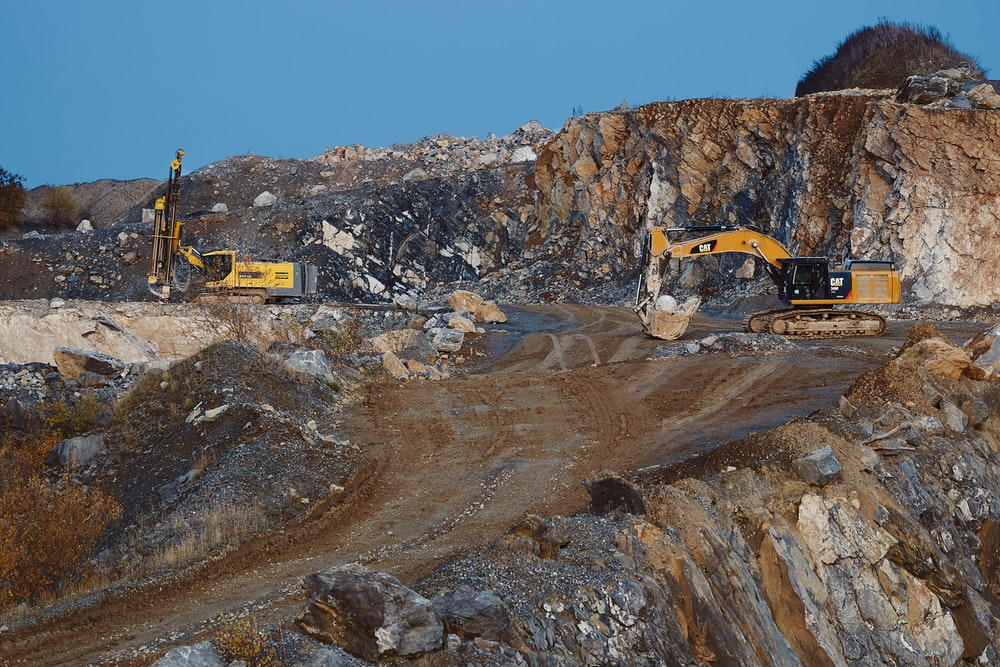 yellow and black excavator on brown rocky mountain during daytime