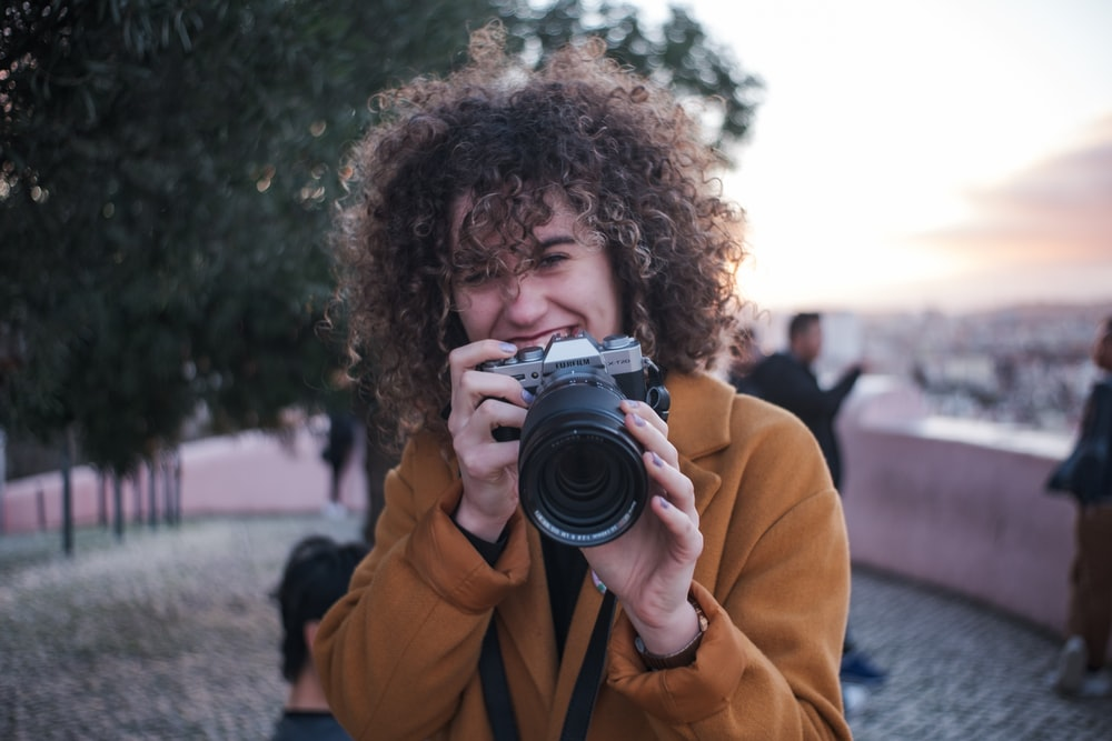 woman in yellow jacket holding black camera