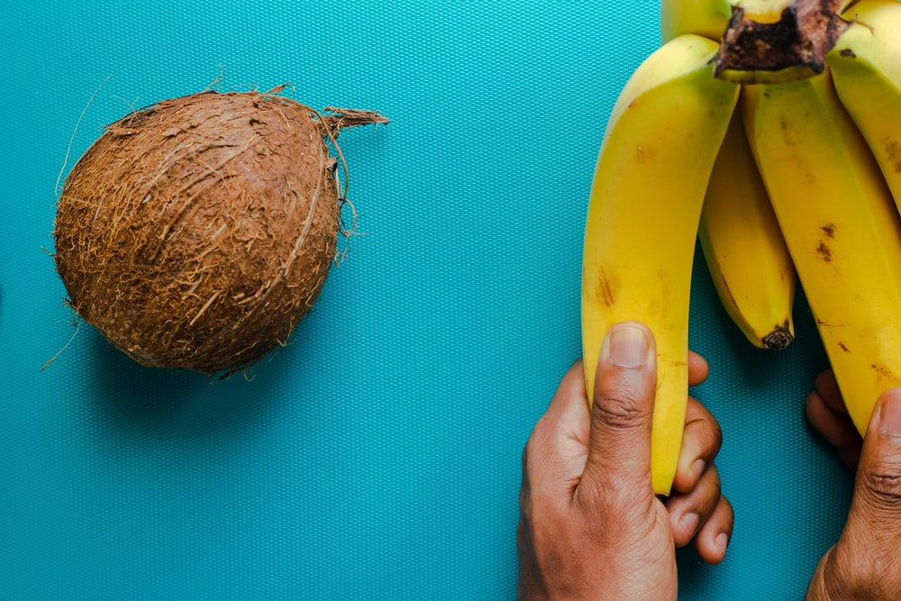 yellow banana fruit beside brown coconut fruit