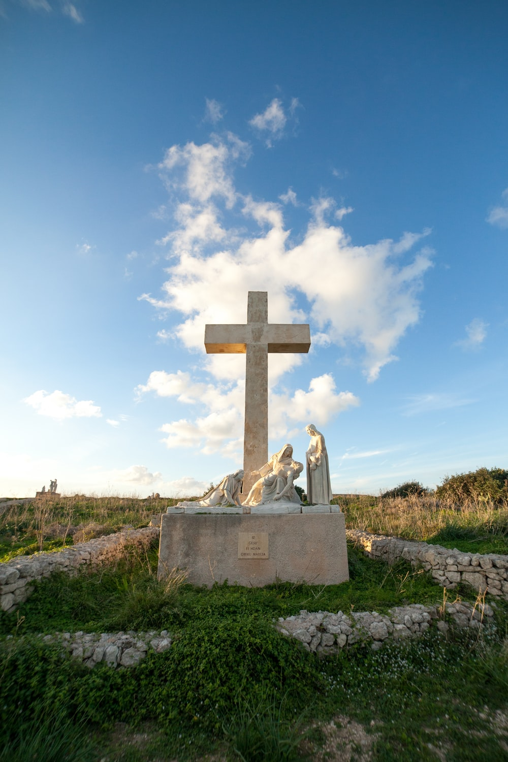 gray concrete cross on green grass under white clouds during daytime