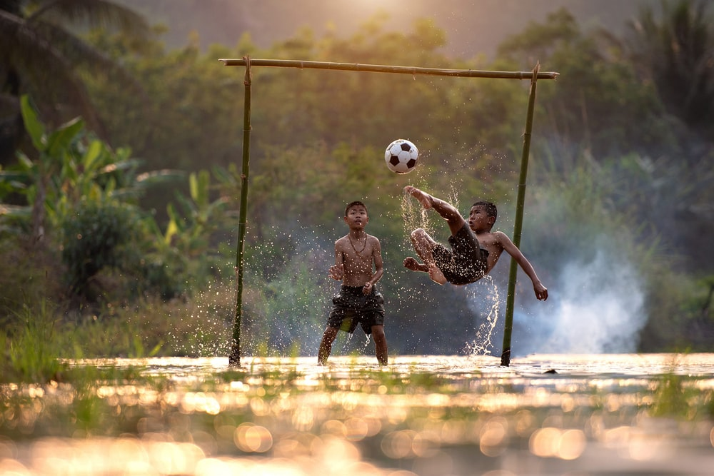 2 boys playing soccer on water during daytime