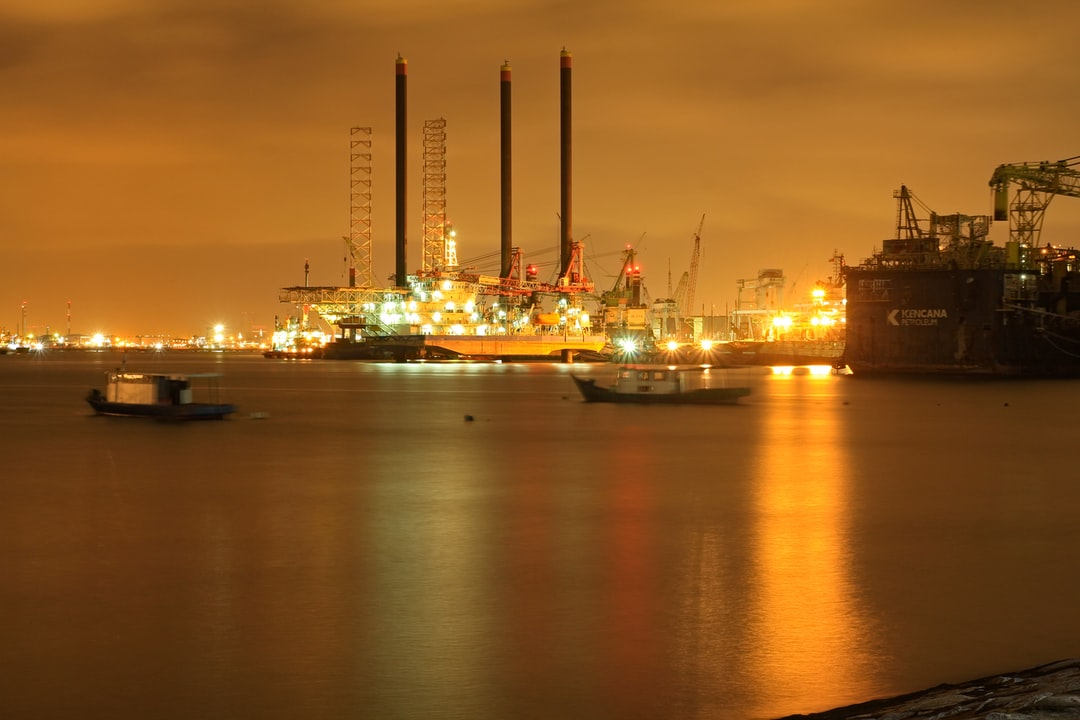 Image of oil refinery at night across the sea.
