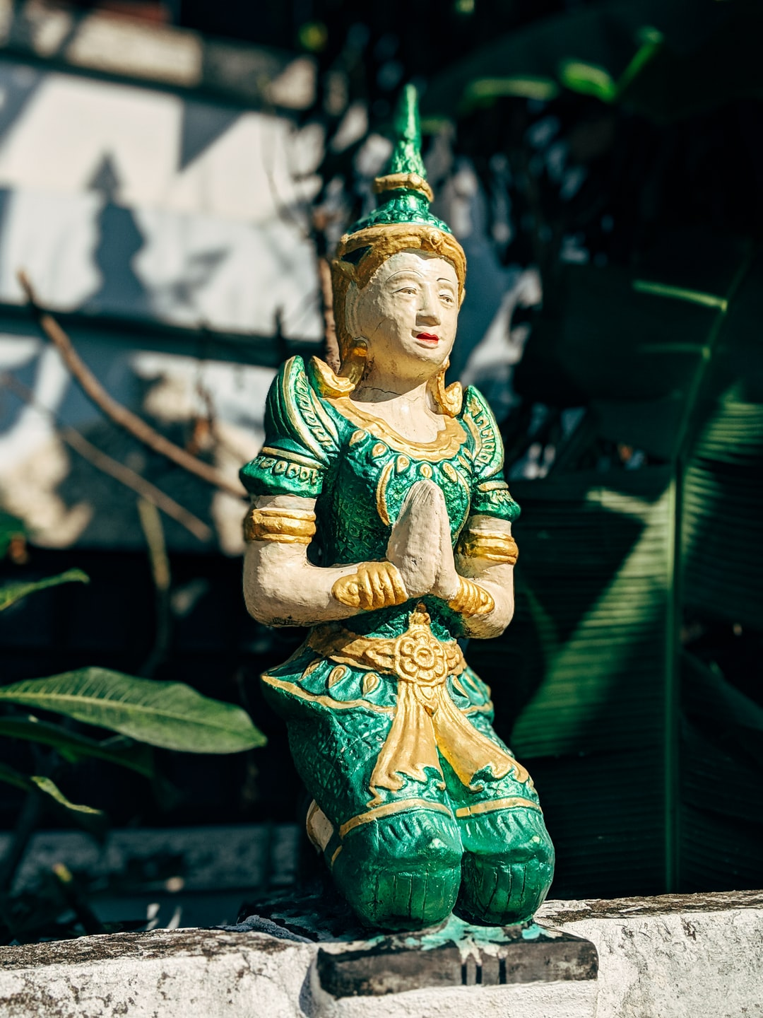 Praying statue with green clothes in Thailand