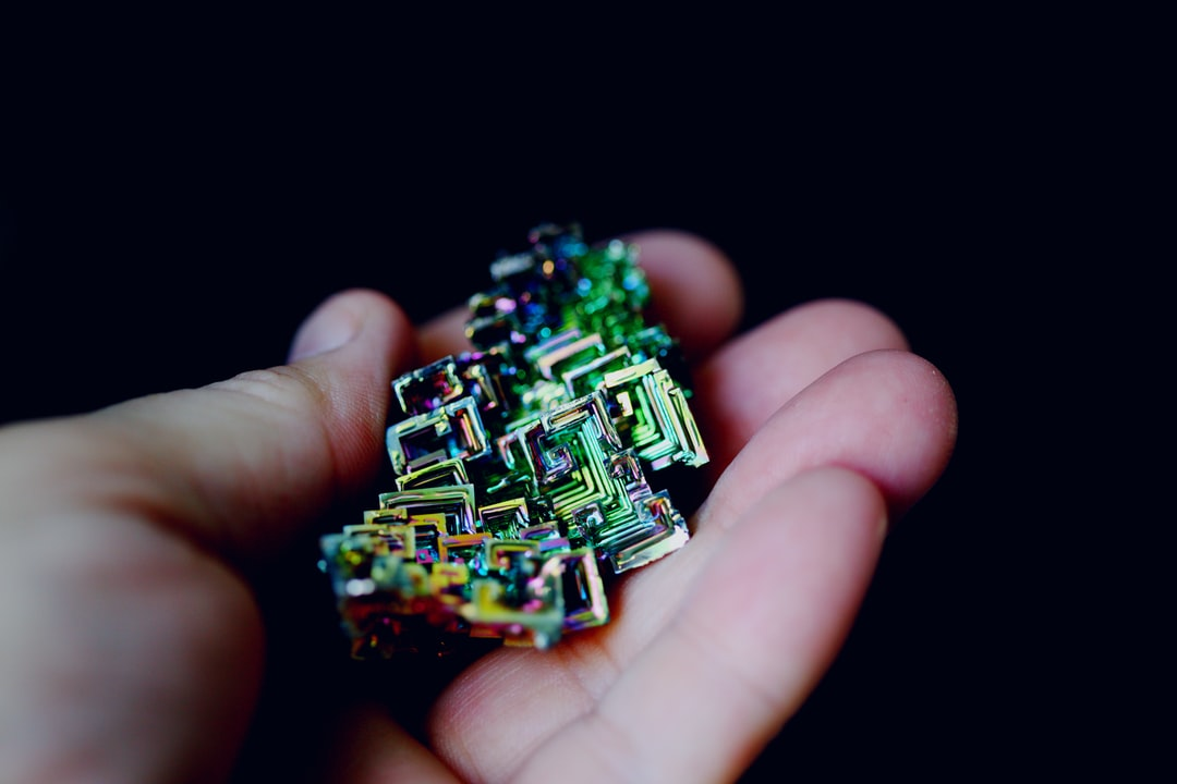 Close up macro image of a hand holding a rainbow bismuth crystal.