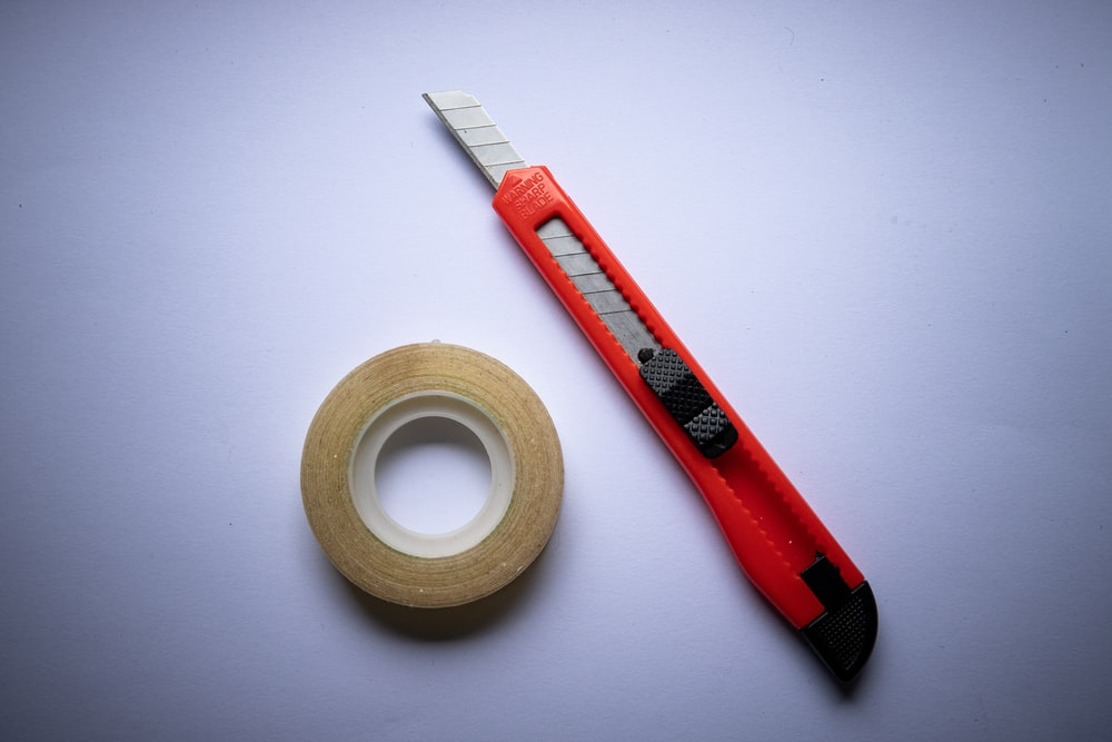 red and black click pen beside white tape roll