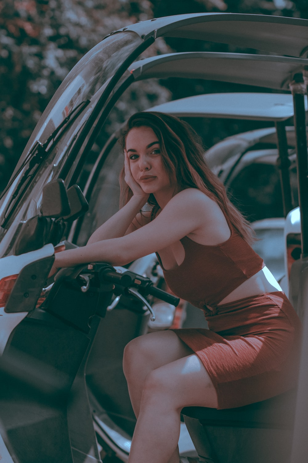 woman in red tank top and red shorts sitting on black car
