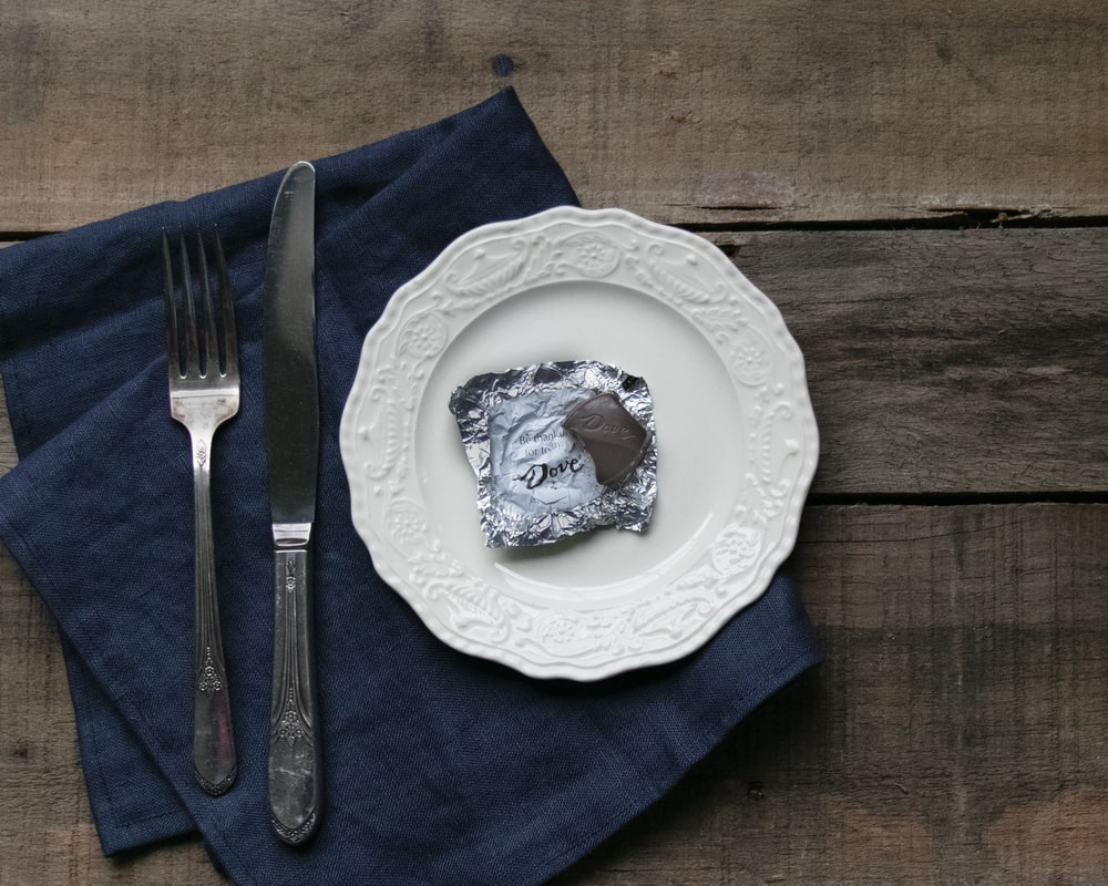 white and blue floral ceramic plate with stainless steel fork and bread knife