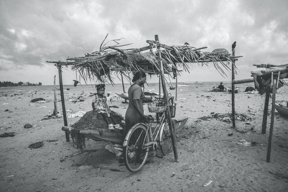 grayscale photo of woman sitting on beach chair under umbrella