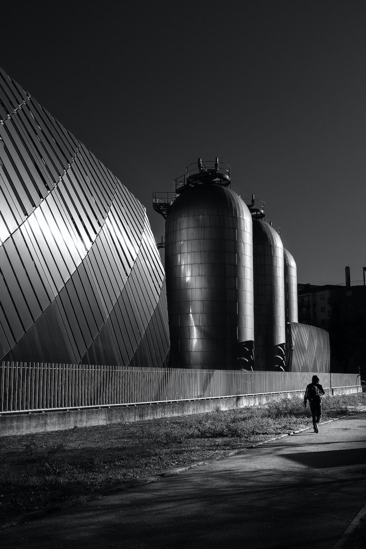 grayscale photo of man walking near building