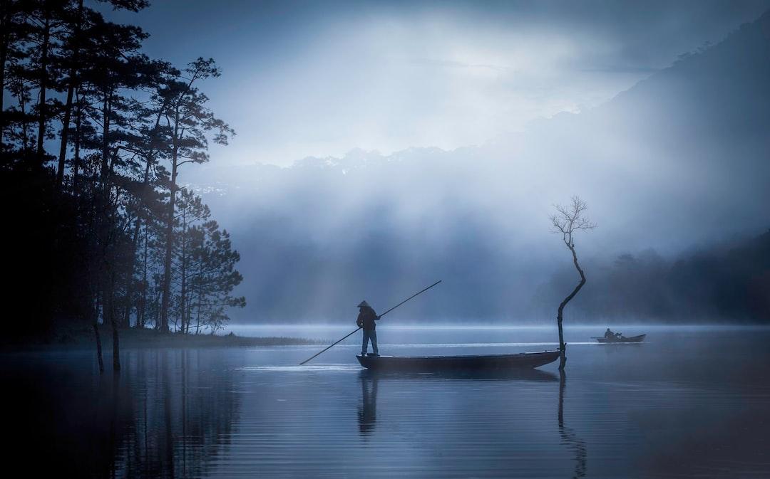 Man In Black Jacket Fishing On Lake During Daytime - unsplash