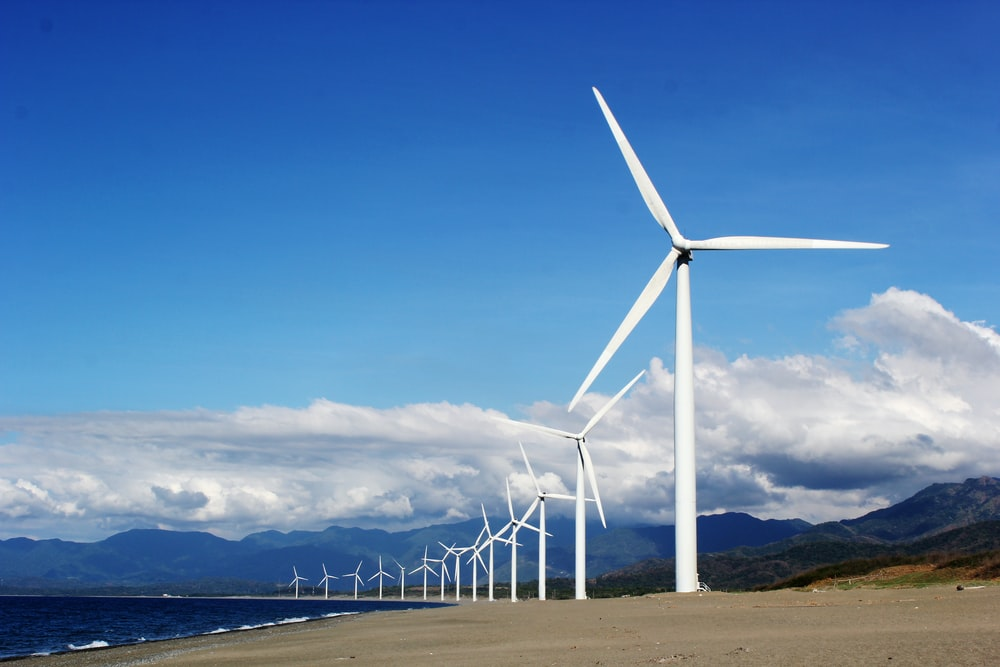 white wind turbines on gray sand near body of water during daytime