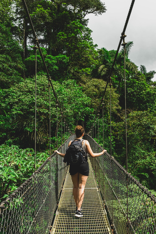 woman in black jacket and black pants standing on hanging bridge