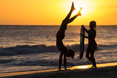 silhouette of 2 women and man standing on beach during sunset barbados teams background
