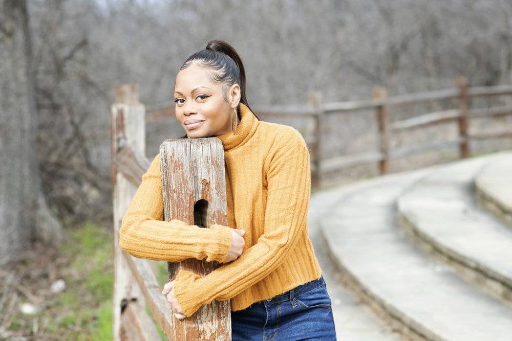 woman in yellow turtleneck sweater and blue denim jeans holding brown wooden post