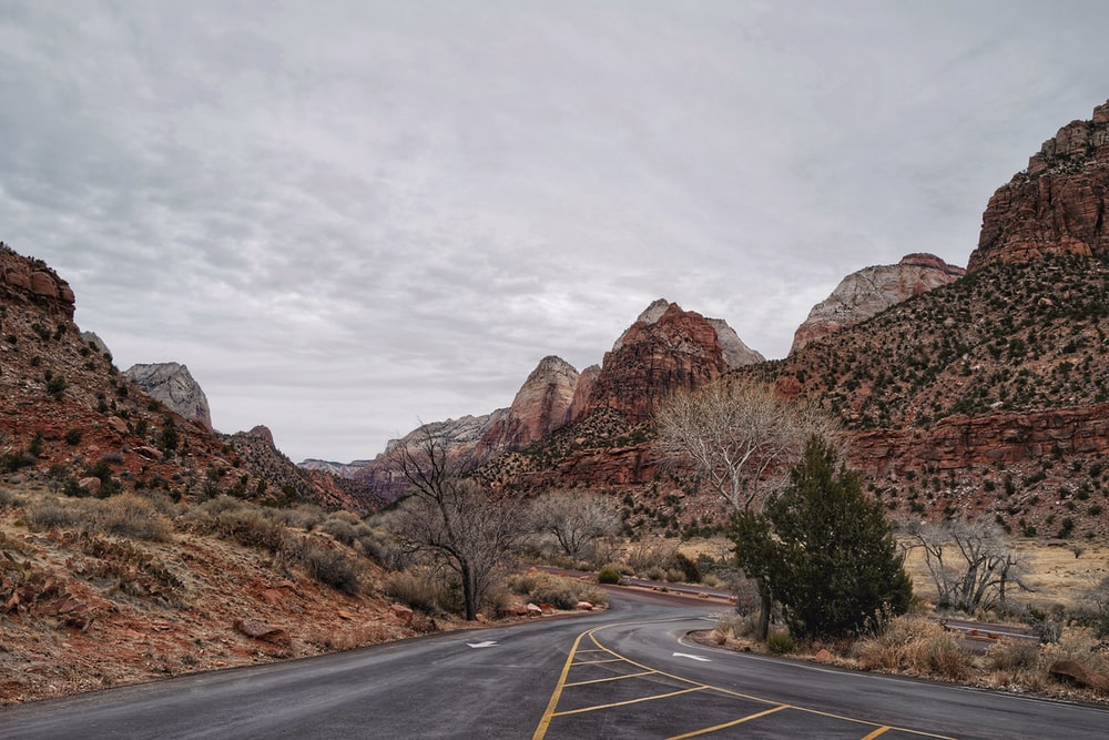 gray concrete road near brown rocky mountain under white sky during daytime