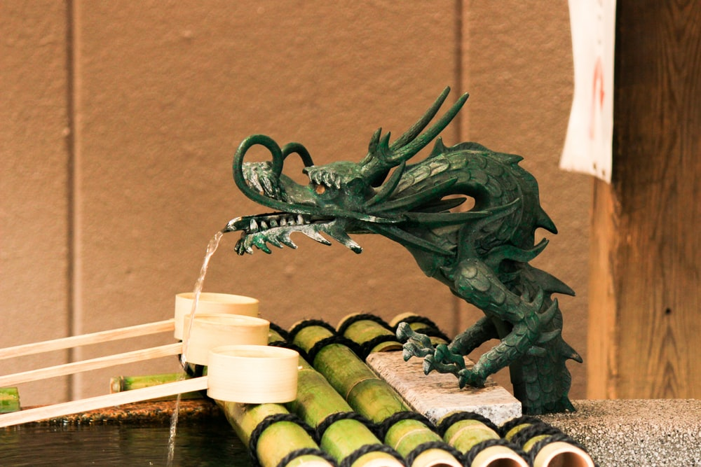 green dragon figurine beside white candles