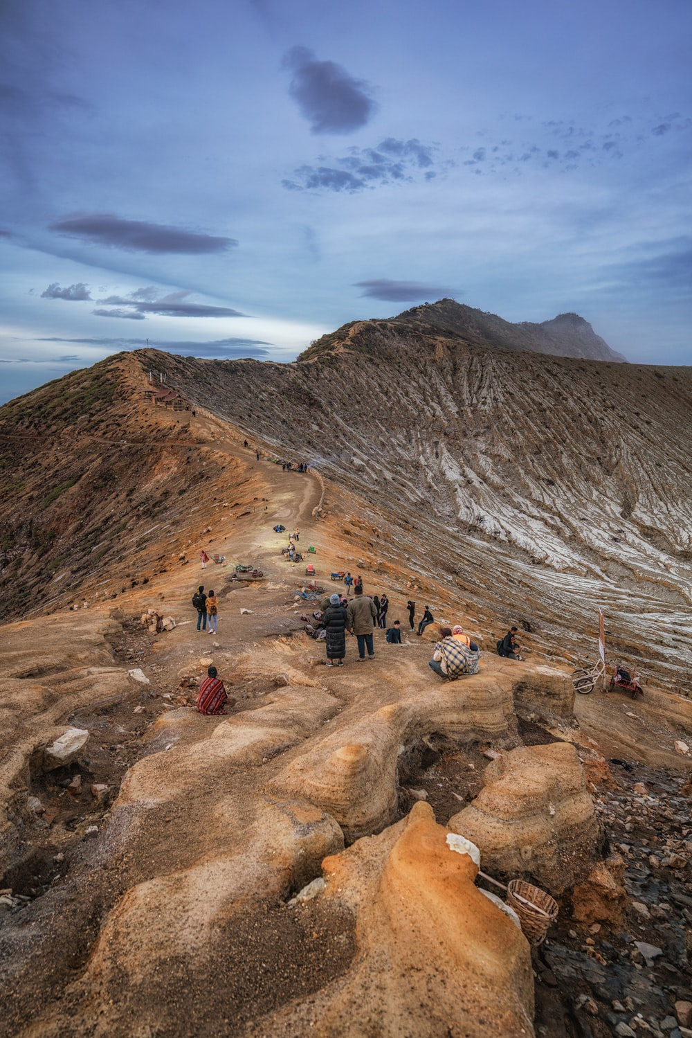 people walking on rocky mountain under blue sky during daytime