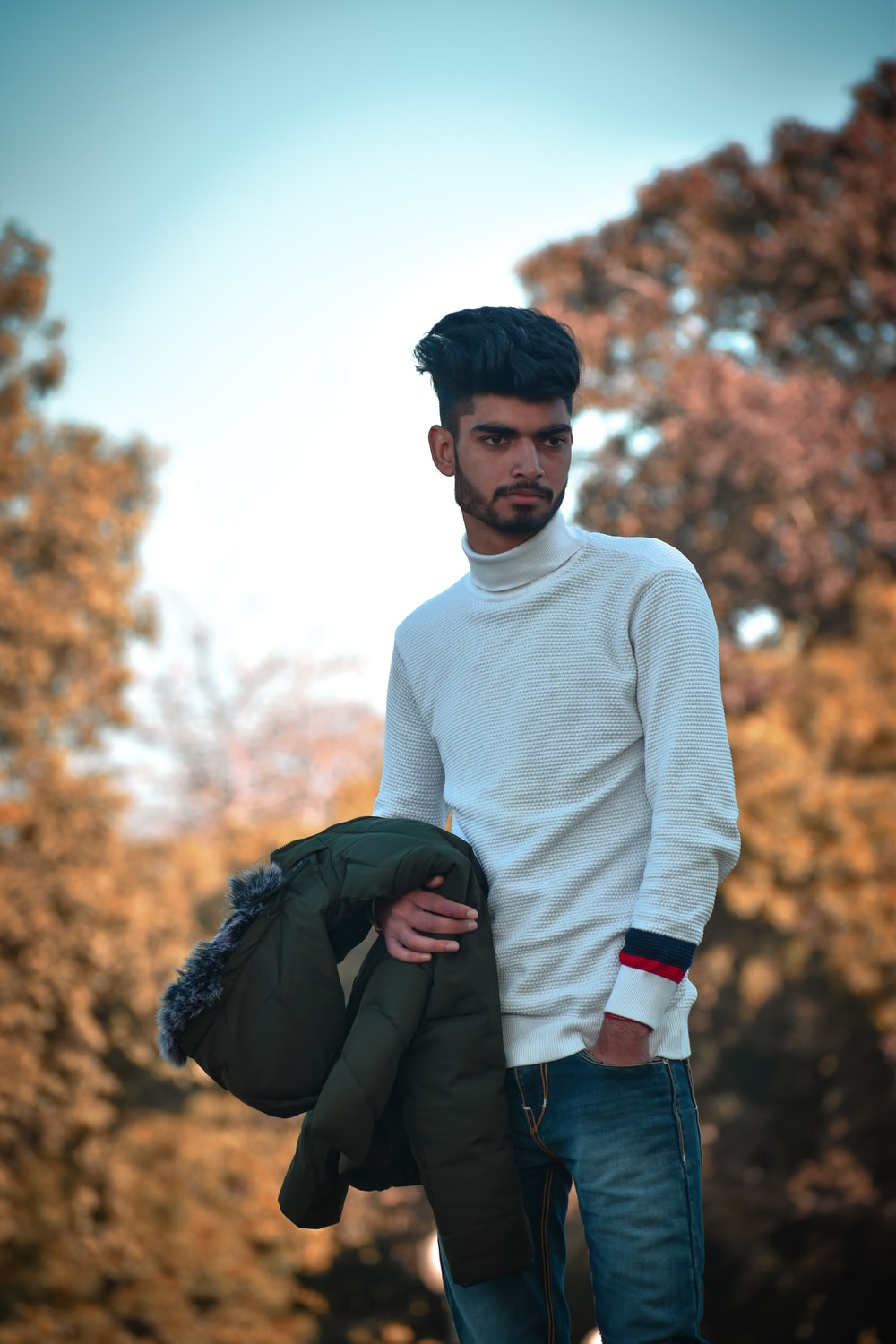 man in white sweater holding black textile