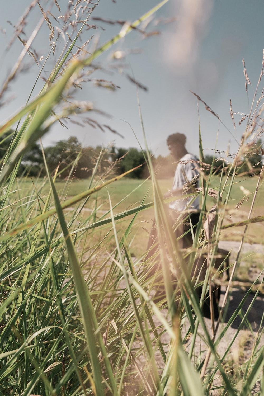 man in white shirt walking on green grass field during daytime